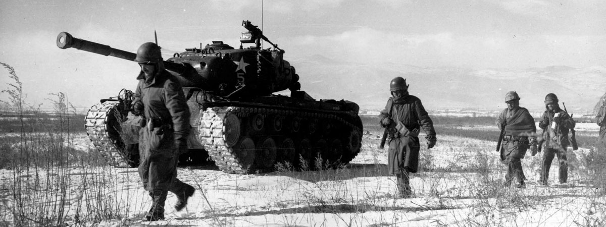 US Army tank escorted by soldiers on foot. (Black & White photo.)